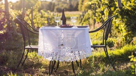Foto de Mesa para una cena romántica al aire libre. Botella de vino junto a dos vasos vacíos - Imagen libre de derechos