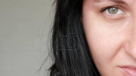 Photo pour Gros plan de la moitié d'un visage de femme. La jeune fille examine son problème de peau avec des pores dilatés, le touchant avec sa main. Le concept de soins pour les problèmes de peau, le vieillissement, l'impact environnemental sur la peau. 4K - image libre de droit