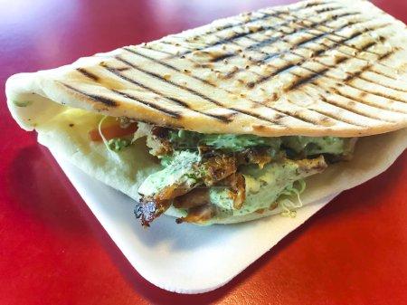 Photo pour Kebab de donateur turc épicé rempli de viande rôtie, de salade fraîche et de sauce à l'ail dans une tortilla grillée. Photo Studio - image libre de droit