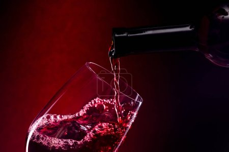 Photo for Pouring red wine into the glass over red background - Royalty Free Image