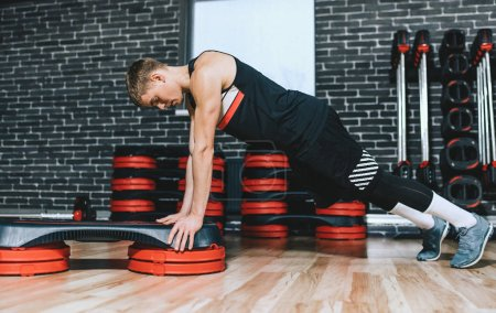 Photo for Sporty athlete trainer man doing on stepper pushups in aerobic fitness club. The handsome male is exercising his chest on the stepper in the modern gym. Sport, lifestyle and people concept. - Royalty Free Image