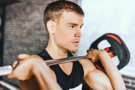 Photo for Close-up portrait of sporty muscular fitness man preparing to deadlift a barbell over his head in modern fitness club. Functional training with barbell at the gym. Sport, people and healthy lifestyle - Royalty Free Image