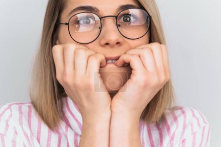 Photo for Cropped head closeup portrait of young female with scared and anxious expression, bites finger nails, wears striped pink shirt and round glasses, being afraid. Negative emotions concept. - Royalty Free Image