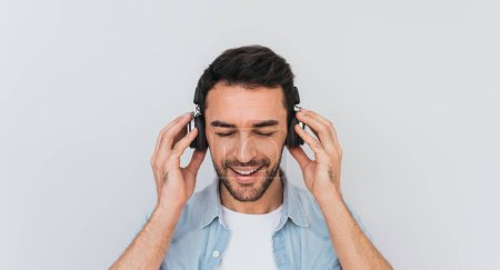 Photo for Portrait of unshaven handsome young Caucasian male with cheerful expression, closes eyes as feels enjoyment and happiness, holding headphones with both hands, listening music in studio. Copy space - Royalty Free Image