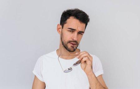 Photo pour Sexy grave jeune barbu mâle vêtu de T-shirt blanc casual, garde lunettes de soleil à la main, regardant devant la caméra, isolée sur fond blanc de béton. Gens, lifestyle, concept de mode - image libre de droit