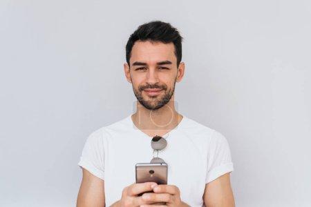 Photo pour Barbu de race blanche gai au large sourire maintenant être téléphone intelligent heureux d'utiliser Internet sans fil gratuit pour les médias sociaux. Copiez l'espace pour votre publicité, informations textuelles. Gens, technologie - image libre de droit