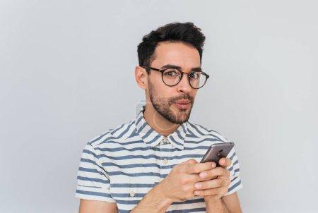 Photo pour Closeup portrait d'étonné élégant jeune homme avec des lunettes tendances porte chemise rayée, détient téléphone intelligent en mains, utilise une connexion internet gratuite pour les réseaux sociaux ou des messages, à la recherche sur l'appareil photo. - image libre de droit
