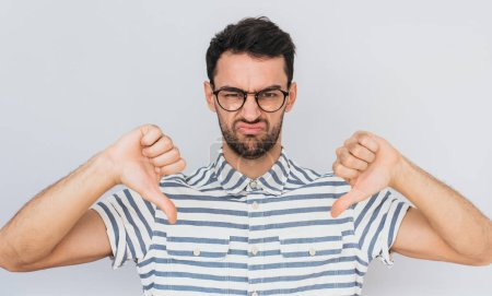Photo for Handsome unhappy male wears round trendy glasses, striped shirt looking at the camera with negative expression, showing thumbs down with both hands. Body language and emotion concept - Royalty Free Image