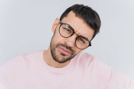 Closeup self portrait of serious macho man wears trendy round glasses and pink clothes posing isolated over white background in studio wall. People, lifestyle and emotion concept.