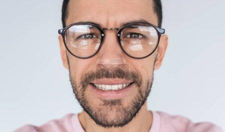 Foto de Recortada Closeup retrato de joven guapo serio barbudo modelo masculino mira a la cámara, lleva gafas de moda ronda con sonrisa toothy. Primer plano de hombre en espectáculos, ropa rosa anuncia en estudio. - Imagen libre de derechos