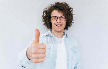 Photo pour La race humaine, les émotions humaines positives et les expressions. Heureux homme caucasien avec les cheveux bouclés, porte une chemise en denim et des lunettes rondes, montrant pouces vers le haut pour le succès et la réalisation, sur le mur blanc studio . - image libre de droit