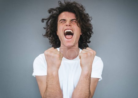 Photo for Excited successful handsome young male wears white t-shirt, clenches fists in joy, scream with opens mouth widely as exclaims with happiness, isolated over grey studio background. Advertisement space - Royalty Free Image