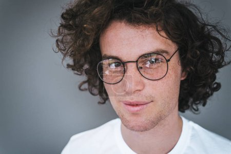 Photo for Closeup view portrait of handsome young male model with curly hair, wearing white t-shirt and round trendy spectacles, looking at the camera. Copy space for advertisement. People concept. - Royalty Free Image