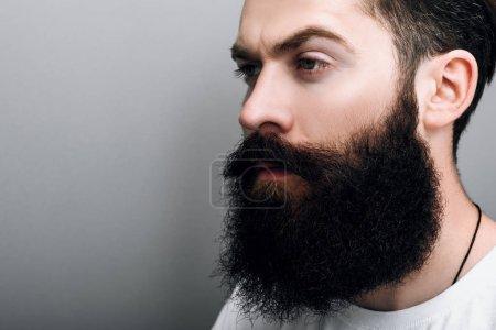 Foto de Recorta cerca retrato de brutal macho caucásico con moda barba y bigote, posando sobre fondo gris studio. Modelo de hombre europeo barba barbero con seguro de expresión en su rostro - Imagen libre de derechos