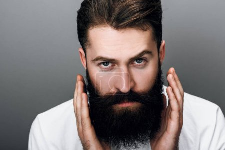 Photo for Cropped horizontal close up portrait of brutal handsome young bearded male corrects his moustache and beard, looking at the camera in white tshirt, on a gray - Royalty Free Image
