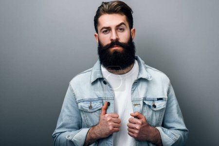 Handsome fashionable young European male with thick beard wearing trendy denim jacket, staring at camera with serious and cheerful look. Barber man posing against gray studio wall.