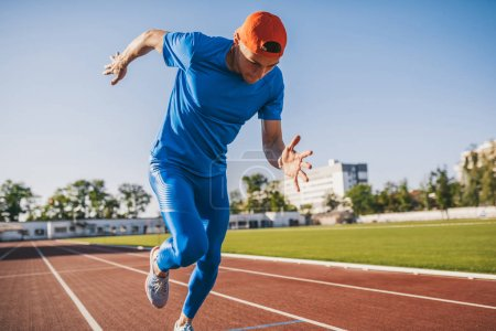 Photo for Handsome professional young Caucasian male athletic running and jogging alone along a race track in stadium while out training on a sunny day. Sport, lifestyle and people concept. - Royalty Free Image