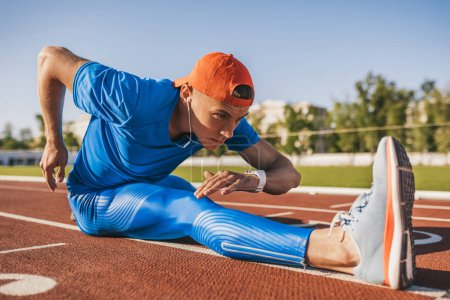 Photo for Horizontal shot of athlete runner young male stretching his leg on a running track in stadium, preparing for working out. Caucasian man exercising outdoors wearing blue sportswear. Sport and people - Royalty Free Image