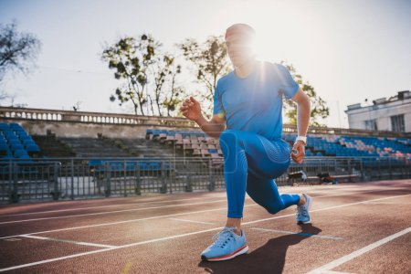 Photo for Muscular athlete young male stretching his leg on a running track in stadium, preparing for running and jogging. Caucasian man exercising outdoors activity wearing blue sportswear. Sport and people - Royalty Free Image