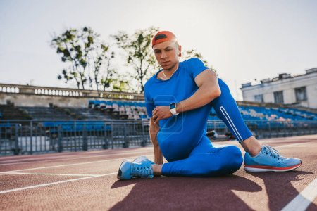 Photo pour Athlète attrayant jeune mâle s'étendant sa jambe sur une piste d'athlétisme dans le stade, préparation pour running et jogging. Homme caucasien exercice en plein air activité portant des vêtements de sport bleu. Sport et people - image libre de droit
