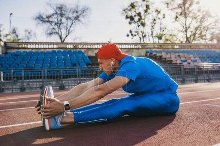Photo pour Remise en forme athlète attrayant jeune mâle s'étendant sa jambe sur une piste d'athlétisme dans le stade, préparation pour running et jogging. Homme caucasien exercice en plein air pour marathon. Sport et people - image libre de droit