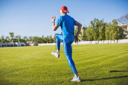 Photo pour Vue arrière horizontal active jeune athlète masculin running et jogging seul le long d'une pelouse verte de football au stade alors que la formation sur une journée ensoleillée. Concept sport, mode de vie et les gens. - image libre de droit