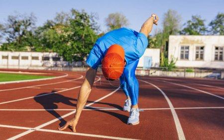 Photo pour Mâle d'athlète professionnel jeune sprinteur à prêt à commencer une course position de départ. Sprinter homme prêt à l'exercice de sports sur piste au stade. Concept sport, mode de vie et les gens. - image libre de droit