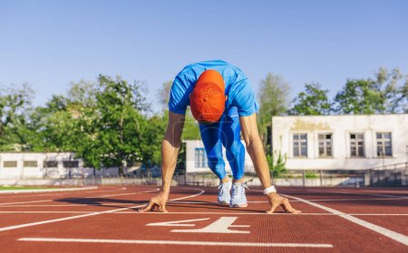 Photo for Sport, lifestyle and people concept. Sprinter athlete male at starting position ready to start a race. Man sprinter ready for sports exercise on racetrack in stadium. - Royalty Free Image