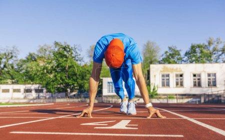 Photo pour Concept sport, mode de vie et des personnes. Mâle d'athlète Sprinter à prêt à commencer une course position de départ. Sprinter homme prêt à l'exercice de sports sur piste au stade. - image libre de droit