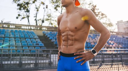 Photo for Cropped head portrait of topless an athlete male standing on a running track with hands on waist. Runner man getting ready to run standing at the line race track, weraing blue sportswear.Sport, people - Royalty Free Image
