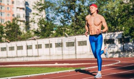 Photo pour Beau jeune athlète masculin caucasien actif courir et faire du jogging seul le long d'une piste de course dans le stade tout en s'entraînant pour le marathon par une journée ensoleillée. Concept sport, mode de vie et personnes . - image libre de droit