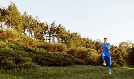 Photo for Image of young fit male runner exercising on green grass in the park. Horizontal shot of handosme athlete running and sprinting outdoor preparing for marathon. Sport and people concept. - Royalty Free Image