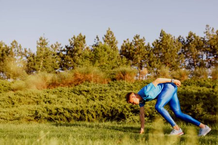 Photo for Horizontal side view shot of fit young male sprinter at starting position ready start in the park. Handosme athlete running outdoor preparing for marathon in mountain. Sport and people concept. - Royalty Free Image