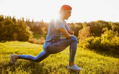 Foto de Athlete male stretching on a green grass in the park, preparing for running and jogging. Caucasian runner exercising outdoors for marathon in mountain. Sport and people concept. - Imagen libre de derechos