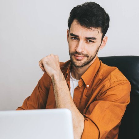 Photo for Indoor portrait of confident young Caucasian male in shirt, sitting at his office, enjoying high-speed internet connection on open notebook computer. - Royalty Free Image