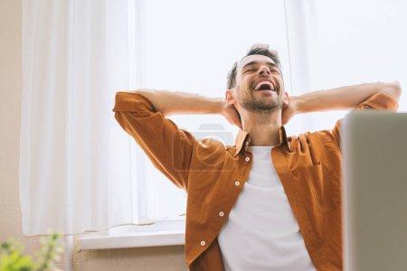 Photo pour Tête d'homme d'affaires heureux avec le sourire enjoué, réalisation des objectifs de vie. Concept de succès et de réussite. Étudiant du Caucase heureux assis à côté de l'ordinateur et vous détendre avec les mains derrière la tête. - image libre de droit