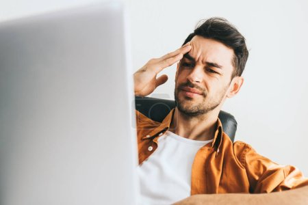 Photo for Young Caucasian man in casual clothes have headache behind computer. Frustrated young handsome man worried about problems in business. Stressed businessman after long web conversation. - Royalty Free Image