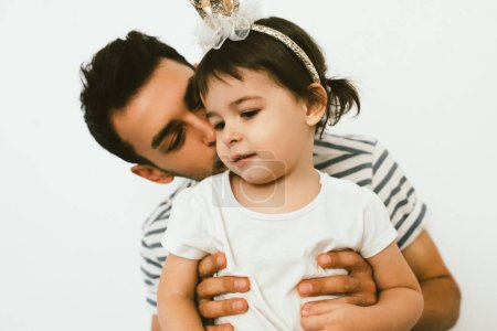 Photo for Horizontal close up shot of cute toddler girl wearing crown, on her birthday embrace with dad against white background. Portrait of joyful father kiss and hug his daughter. Happy relationship family. - Royalty Free Image