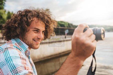 Photo pour Côté vue portrait du jeune photographe souriant aux cheveux bouclés photographier à l'extérieur. Homme caucasien prendre une photos avec l'appareil photo numérique à l'extérieur, photographie de la nature. Notion de peuple, de voyages et de style de vie. - image libre de droit
