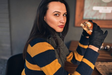 Photo for Outdoor portrait of hungry pretty woman wearing casual sweater, eatting delicious burger while sitting at terrace. Female with red lips, tasting hamburger outside at cafeteria. People, food, lifestyle - Royalty Free Image