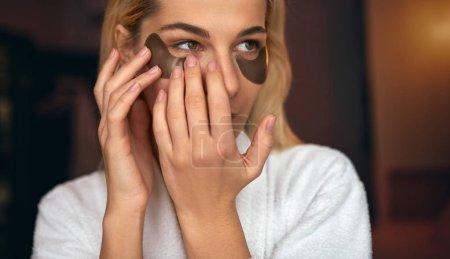 Foto de Closeup retrato de joven atractiva con maquillaje natural pone parches debajo de los ojos de las arrugas y ojeras. Spa de belleza en casa. Mujer joven atractiva en pasar tiempo en casa de baño - Imagen libre de derechos