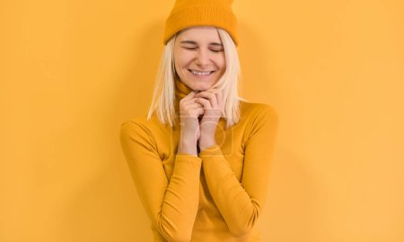 Foto de Cheerful blonde female with positive expression, close her eyes and smiling joyfully, wears yellow clothes, isolated over yellow background. Happy woman feeling excited. People and emotions concept. - Imagen libre de derechos