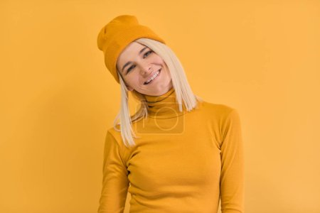 Photo for Monochrome studio portrait of happy Caucasian woman with positive smile, has blonde hair, looking to the camera, isolated on yellow wall. People and emotions concept - Royalty Free Image