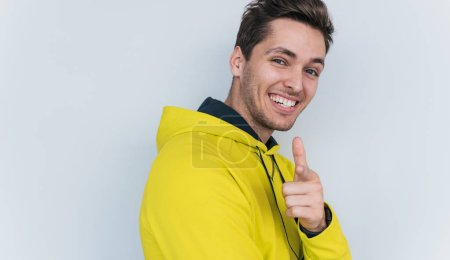 Photo for Happy male in yellow hoodie with toothy smile isolated on white background - Royalty Free Image