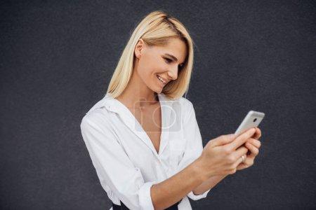 Photo pour Portrait de jeune femme textos message sur téléphone portable et posant sur le mur gris - image libre de droit