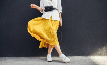 Photo for Horizontal cropped image of stylish slim woman in beautiful yellow skirt - Royalty Free Image