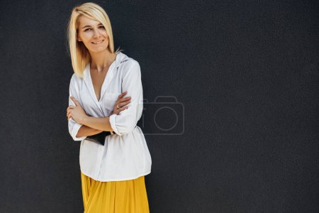 Photo for Pretty blonde female standing with arms crossed and looking at camera - Royalty Free Image