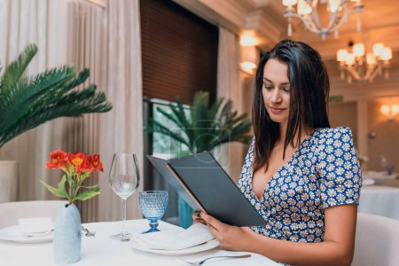 Photo pour Jeune femme assise au restaurant avec un menu pour le déjeuner - image libre de droit