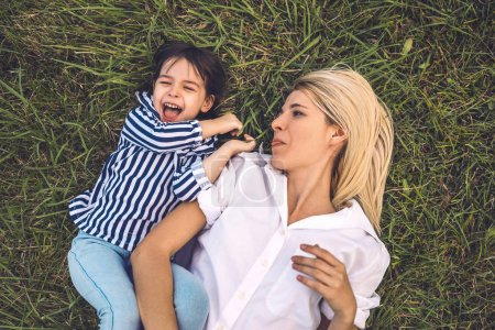 Photo pour Frais généraux coup d'heureux femme assez drôle jouer et couché sur l'herbe verte extérieure avec son adorable petite fille. Tendre mère et fille de passent du temps ensemble dans le parc. Maman et enfant sont amuser à l'extérieur - image libre de droit
