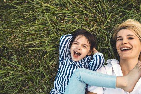Photo pour Frais généraux cropped image d'heureuse belle femme rire et jouer avec son adorable petite fille sur l'herbe verte en plein air. Tendre mère et fille de passent du temps ensemble dans le parc. Maman et enfant sont amuser - image libre de droit